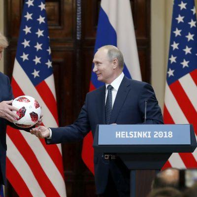 Vladimir Putin ojentaa Donald Trumpille jalkapallon