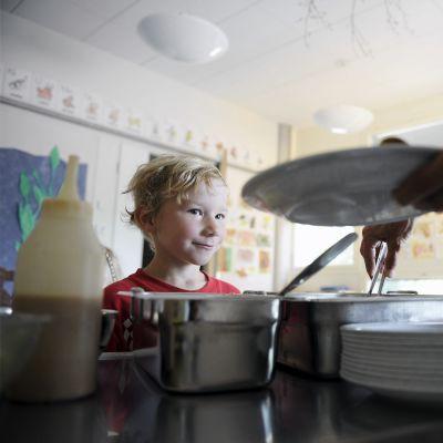 Ruokaa annostellaan lautaselle päiväkodissa.