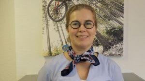 Kvinna i lila skarf och glasögon ser rakt in i kameran och ler.