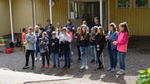 En grupp elever står framför en skolbyggnad. De klappar händer och sjunger.
