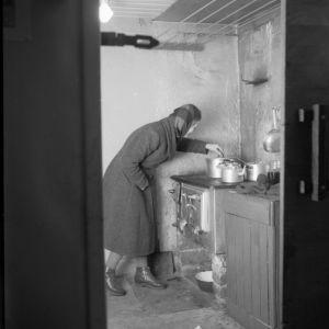 Kellarissa asuvan perheen äiti hellan ääressä (1956)