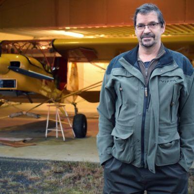 Jorma Hakkarainen framför ett gult, ultralätt flygplan.