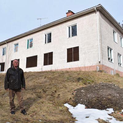 Greger Lindholm står framför det stängda daghemmet Pjånkis i Kimito. Grått vårlandskap.