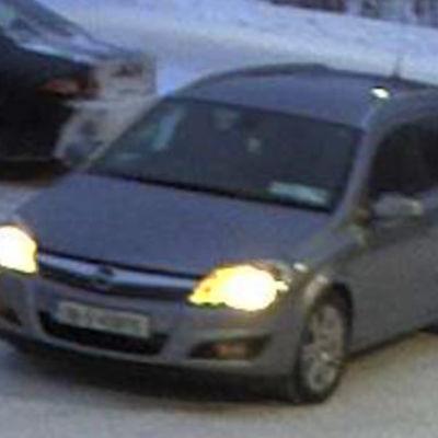 En suddig bild på en grå bil av märket Opel.