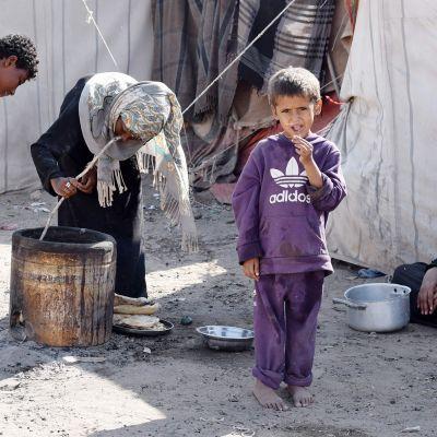 Jemeniläinen tyttö valmistaa ruokaa avustusleirissä Adenissa.