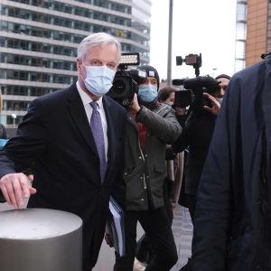 EU:s brexitförhandlare Michel Barnier går med munskydd på mot pressen i Bryssel.