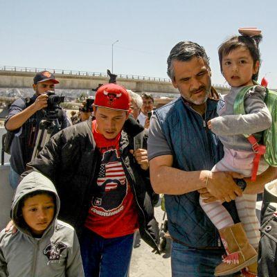 Kaksi miestä kantaa lapsia Yhdysvaltain ja Meksikon rajalla.
