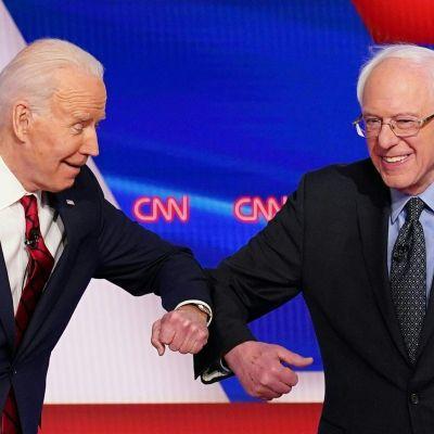 Två kostymklädda män ler mot varandra. Männen är Bernie Sanders och Joe Biden.