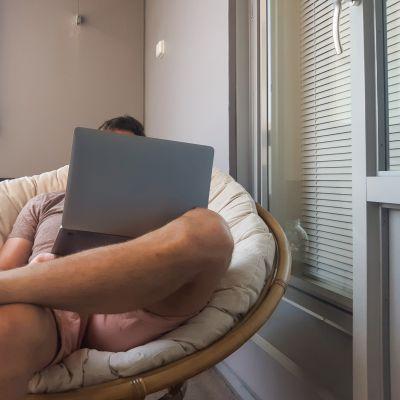 Henkilö istuu parvekkeella tuulettimen ja tietokoneen kanssa.