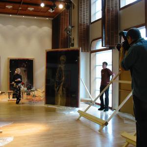 Suuressa näyttelysalissa kaksi suurta taulua. Oikealla mies valokuvaa naista ja taideteosta. Heidän välissä keskellä ikkunan edessä seisoo mies.