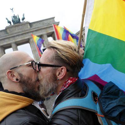 miehet suutelevat, taustalla Brandenburgin portti ja sateenkaarilippuja.