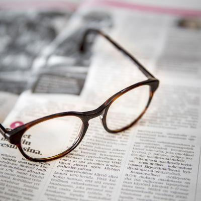 silmälasit sanomalehden päällä
