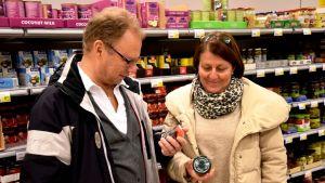 Tom och Martina Blomqvist läser på förpackningarna i en matbutik.