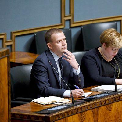 Valtiovarainministeri Petteri Orpo ja perhe- ja peruspalveluministeri Annika Saarikko eduskunnan täysistunnossa.