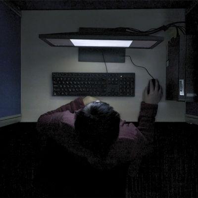 En av innehållsmoderatorerna fotad uppifrån med datorskärmens ljus i ansiktet.