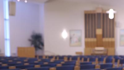 En präst sitter på en stol i en stor sal och pratar.