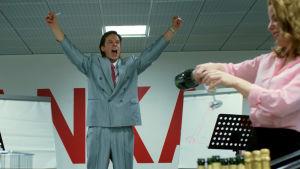 Jari Sarasvuo (Mikko Nousiainen) står på en scen och jublar, i förgrunden häller människor upp champagne.