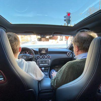 Trafiklärare instruerar en ung elev som kör i en personbil.