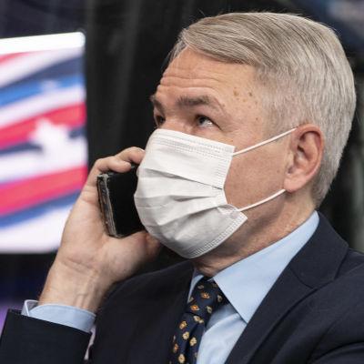 Utrikesminister Pekka Haavisto talar i telefonen iklädd ansiktsskydd