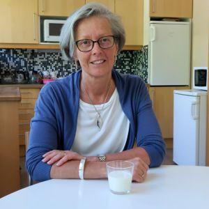 Birgitta Parikka sitter vid ett bord med ett glas mjölk framför sig.