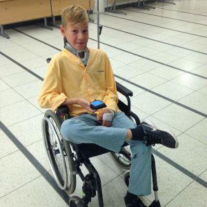adam i en rullstol och han ler