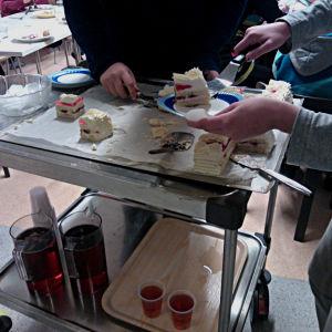 Barn tar åt sig tårta från en bricka på en kärra