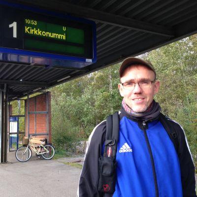 man står på tågstation och väntar på tåget till kyrkslätt