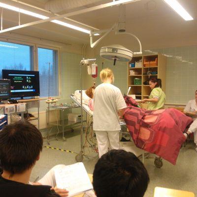 Sjukskötarstuderande på praktisk undervisning med en docka som är kopplad till en hjärtmonitor.