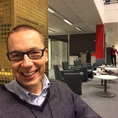 Leende glasögonprydd man med kontorsmiljö i bakgrunden.