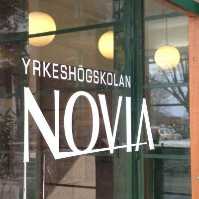 Yrkeshögskolan Novias logotyp klistras på ett fönster. Bilden tagen i Vasa.