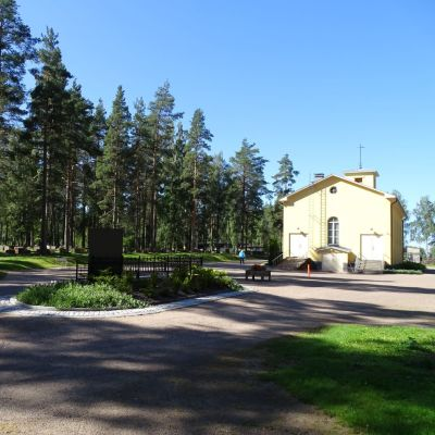 Keltainen kappelirakennus aukion reunalla.