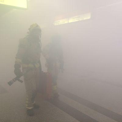 Palomiehiä sankan savun keskellä Sörnäisten metroasemalla pidetyssä pelastusharjoituksessa.