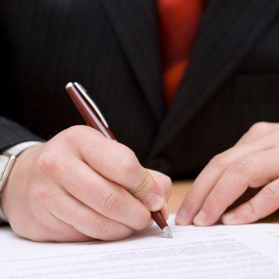 mies allekirjoittaa paperia
