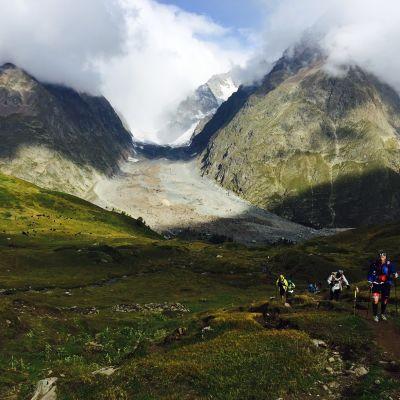 Löpare och bergstoppar i bakgrunden.