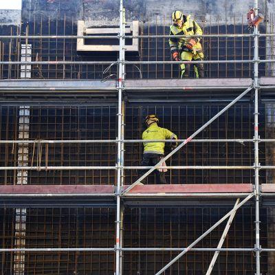 Työnteijöitä rakennustelineillä kauppakeskus Triplan rakennustyömaalla.