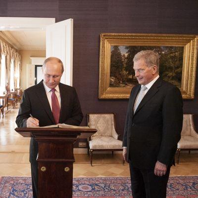 Presidentti Vladimir Putin kirjoittaa Presidentinlinnan vieraskirjaan.