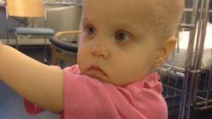 Yksivuotias lapsi, Selma, Lasten syöpäosastolla vaaleanpunainen sairaala-asu yllään.