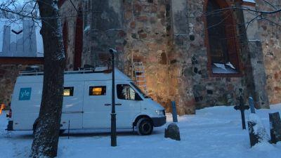 Yles vita sändningsbil står utanför en kyrka. Det är snö på marken.
