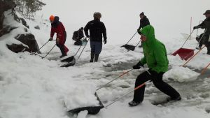 Frivilliga skottar upp snödrivor för saimenvikare.