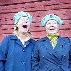 Kaksi naista siniset lakit päässään ja takit päällään ilveilevät naamoillaan