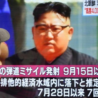 Mies katsoo kuvaa, jossa on Pohjois-Korean johtaja Kim Jong-un.