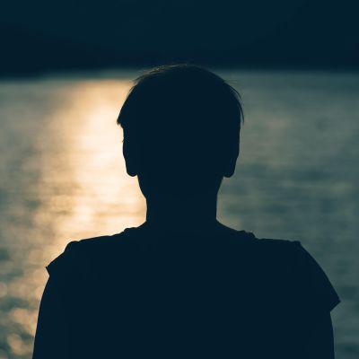 nuoren silhuetti järven rannalla
