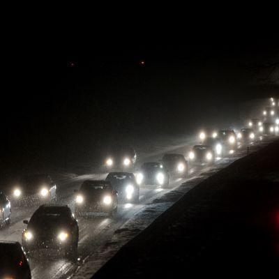 Autoja ajaa pimeässä illassa ja lunta satelee hiljalleen.