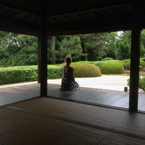 Nainen takaapäin puisen temppeliterassin reunalla katselemassa puutarhaa.