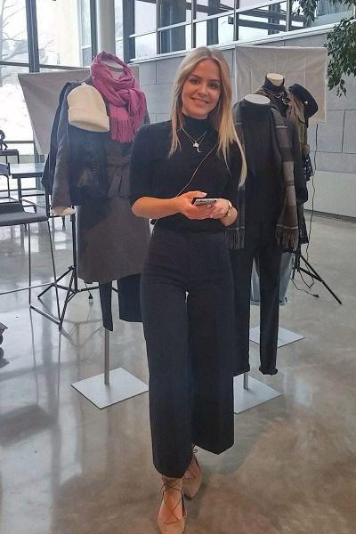 En kvinna med blont hår och svarta kläder. Hon står framför provdockor  klädda i vinterkläder c1d409b7a2cf3