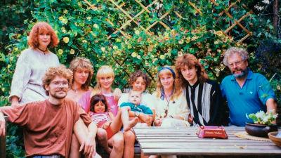 Ett familjeporträtt i trädgården. Familjen är samlad runt ett trädgårdsbord med en grön häck i bakgrunden.