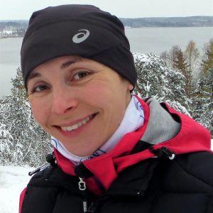 Leende kvinna i vinterlandskap.