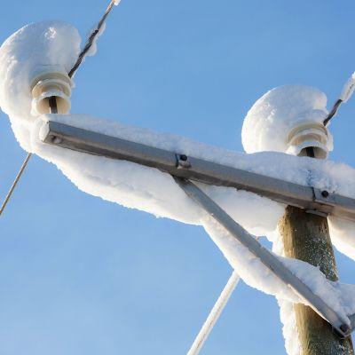 sähkölinja lumen peitossa