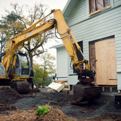 En grävskopa gräver framför ingången till ett gammalt stockhus.