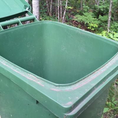 En grön soptunna av plast med skog i bakgrunden
